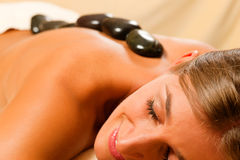 Woman having a hot stone therapy session. Woman in wellness and spa setting having a hot stone therapy session Stock Photography