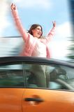 Woman having hun standing in car with arms raised Royalty Free Stock Images