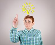 Woman having an idea with light bulb above her head stock photography