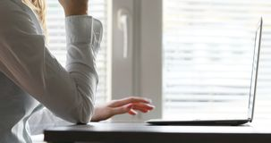 Woman having an idea typing at the computer. Hands of a woman typing at her laptop keyboard, then stopping to search for an idea, and having it stock video