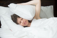 Woman having insomnia. Portrait of young woman lying in bed and covering her ears with pillows from noise. Female model with irritated expression having problems Royalty Free Stock Photo