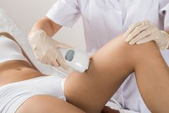 Woman having laser treatment at beauty clinic. Close-up Of Woman Having Laser Treatment At Beauty Clinic On Thigh stock images