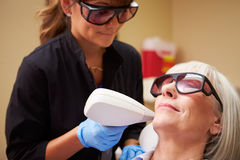 Woman Having Laser Treatment At Beauty Clinic. Lying Down Wearing Protective Goggles stock image
