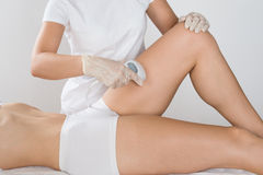 Woman Having Laser Treatment On Thigh. Close-up Of Young Woman Having Laser Treatment On Thigh At Beauty Clinic stock photos