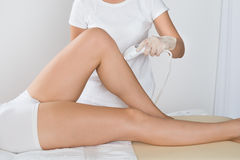 Woman Having Laser Treatment On Thigh. Close-up Of Young Woman Having Laser Treatment On Thigh At Beauty Clinic stock images