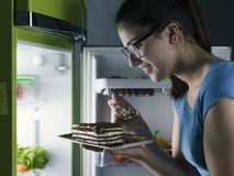 Woman having a late night snack. Woman in the kitchen having a late night snack, she is taking a delicious dessert from the fridge, diet fail concept royalty free stock photography