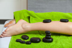 Woman having legs massage with hot stones Stock Photography