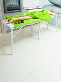 Woman having legs massage with hot stones Stock Photos