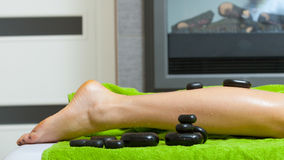 Woman having legs massage with hot stones Stock Image