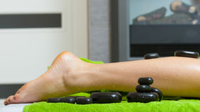 Woman having legs massage with hot stones Royalty Free Stock Photography