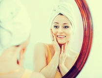 Woman having a look at her face at the mirror Royalty Free Stock Images