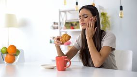 Woman having lunch, eating croissant with coffee, feeling toothache from sweets. Stock photo royalty free stock image