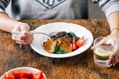 Woman having lunch fried prunes oat cutlets black quinoa. Woman is having lunch fried prunes oat cutlets with black quinoa stock photos