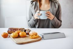 Woman having lunch with her friend, gossiping and enjoying chit-chat. Ordinary slender woman drinking coffee, watching royalty free stock image
