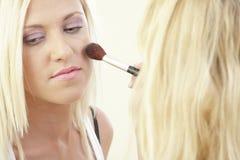Woman having makeup applied Stock Photo