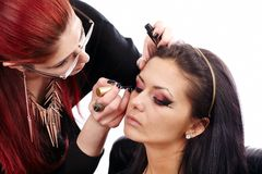Woman having makeup applied by makeup artist Stock Photography
