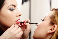Woman having makeup applied by makeup artist Stock Photos