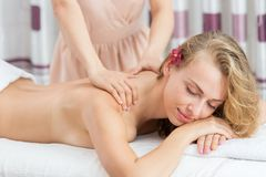 Woman having massage on her shoulder in SPA salon Royalty Free Stock Images