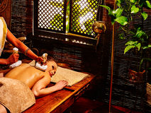Woman having massage with pouch. Green plants outside. Stock Photography