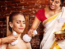 Woman having massage with pouch of rice. Royalty Free Stock Photography