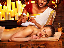 Woman having massage with pouch of rice. Royalty Free Stock Image
