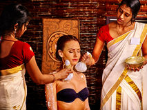 Woman having massage with pouch of rice Stock Images