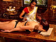 Woman having massage with pouch of rice Royalty Free Stock Photos