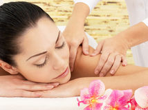 Woman having massage of shoulder in spa salon Stock Photo
