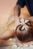 Woman having massage in the spa salon. Body care. Flower in hair Stock Photo