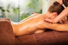 Woman having massage in a spa Stock Photos