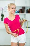 Woman having measuring tape around her waist Royalty Free Stock Photos