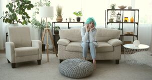 Depressed woman feeling uneasy on sofa at home