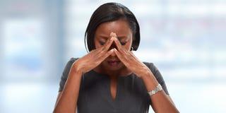 Woman having a migraine headache. Tired black woman with headache migraine. Stress and health Stock Image