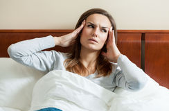 Woman having migraine. Image of woman having migraine lying in bed Royalty Free Stock Photo
