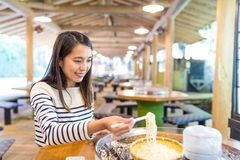 Woman having noodles in japanese restaurant. Asian young beautiful woman portrait Royalty Free Stock Image