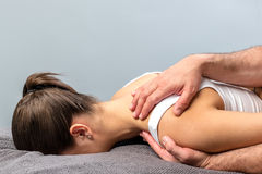Woman having osteopathic shoulder treatment. Close up of detail of woman having physical shoulder treatment.Male therapist hands manipulating scapula stock image