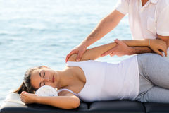 Woman having osteopathic treatment at sea side. Close up of young woman at curative osteopathic shoulder therapy next to sea stock photography