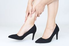 Woman having pain after wearing high heeled shoes. A picture of female feet in pain after wearing high heeled shoes royalty free stock image