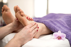 Woman having a pedicure treatment at a spa or beauty salon with. The pedicurist massaging feet royalty free stock photo