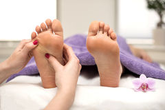 Woman having a pedicure treatment at a spa or beauty salon. With the pedicurist massaging feet royalty free stock photography