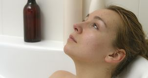 Resting woman in bath. Woman is having a perfect relax in bath. The side view of woman while bathing stock footage