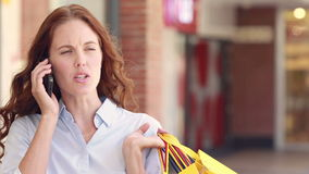 Woman having phone call and holding shopping bag stock video