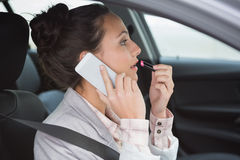 Woman having a phone call while putting on lipstick Royalty Free Stock Photos