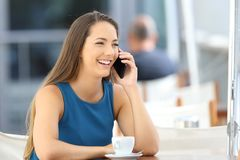 Woman having a phone conversation in a bar. Single woman having a phone conversation sitting in a bar terrace stock images