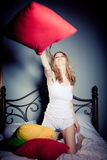 Woman having pillow fight Stock Images