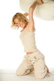 Woman having pillow fight in bed. Young blonde woman having pillow fight in bed royalty free stock image