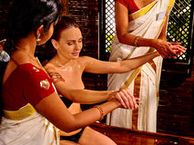 Woman having pouring oil massage in spa Indian salon. Stock Image