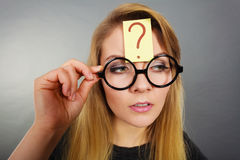 Woman having question mark on forehead thinking Stock Images