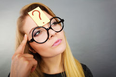 Woman having question mark on forehead thinking Stock Image