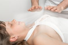 Woman is having reiki healing treatment. Alternative medicine concept stock photos